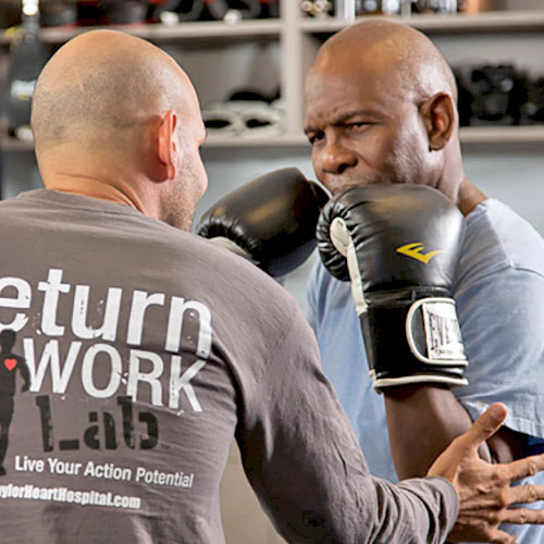 A man trains another man who wears boxing gloves as part of his cardiac rehab