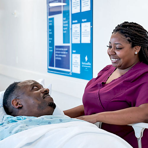 A nurse in magenta scrubs smiles while talking with a male patient lying on a bed on an inpatient floor