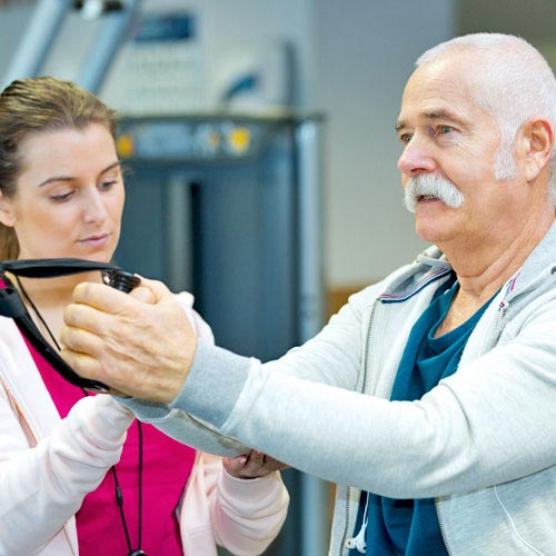 A physical therapist helps a patient use a strengthening machine in the cardiac rehab center