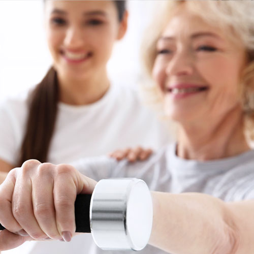 A cardiac rehab aide helps a heart patient who lifts weights as part of her recovery