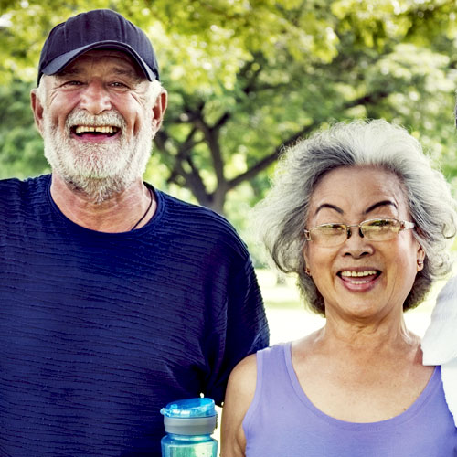 A man holding a water bottle stands next to a woman in the park, both are smiling and happy